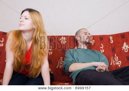 man and woman arguing while sitting on the couch