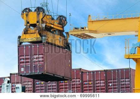Container Cargo Freight Ship With Working Crane Loading Bridge In Dock
