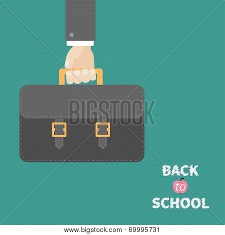 Hand holding black schoolbag briefcase. Flat design style.