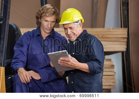 Senior carpenter using digital tablet with colleague in workshop