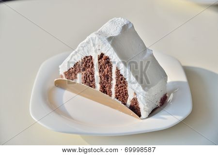 Chocolate Cake With White Cream On A White Table