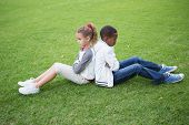 stock photo of not talking  - Young friends not talking to each other after fight in the park - JPG