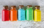 pic of pigments  - Bottles with colorful dry pigments on wooden background - JPG