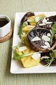 stock photo of portobello mushroom  - Balsamic marinated portobello mushrooms with grilled slices of polenta arugula and shaved parmesan with a balsamic reduction - JPG