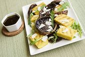 stock photo of portobello mushroom  - Balsamic marinated portobello mushrooms with grilled slices of polenta arugula and shaved parmesan with a balsamic reduction - JPG