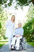 foto of take responsibility  - Pretty nurse taking care of senior patient while taking walk in park - JPG