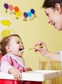 stock photo of homogeneous  - mom giving homogenized food to her daughter on high chair - JPG