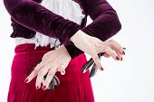 picture of up-skirt  - clouse up hands with castanets of a female spanish flamenco dancer in white blouse and vinous flamenco skirt in studio on gray background - JPG