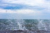 picture of gushing  - Gushing surf of a wave smashing against seaport at Thessaloniki Greece - JPG