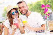 stock photo of lost love  - A picture of a happy couple drinking smoothies in an outside cafe - JPG