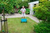 stock photo of potash  - Dutch retired senior fertilising his grass lawn as retirement activity with a blue fertilizer dispenser on wheels - JPG