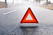 pic of traffic signal  - Bad weather driving - warning triangle on a misty road
