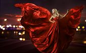 stock photo of flutter  - women dancing in silk dress artistic red blowing gown waving and flittering fabric night city street lights - JPG