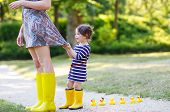 foto of boot  - Mum and little adorable girl in yellow rubber boots family look in summer park - JPG