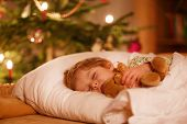 stock photo of boys night out  - Little cute blond boy sleeping under Christmas tree and dreaming of Santa at home indoors - JPG