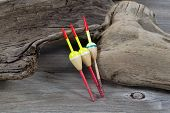 stock photo of driftwood  - Horizontal image of three fishing floats resting against aged driftwood - JPG
