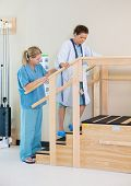 stock photo of upstairs  - Physical therapist assisting female patient in moving upstairs - JPG