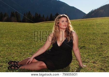 Elegant woman with oversized half lying on a meadow in the Alps
