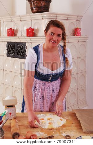 Young woman in dirndl in making a dough
