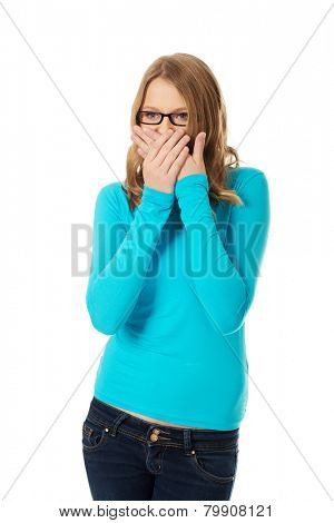 Teenage woman covering mouth because of shame