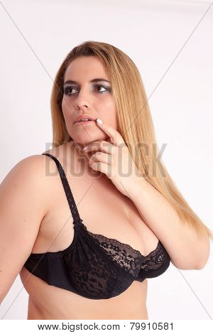 Corpulent, busty woman with long blonde hair and black bra