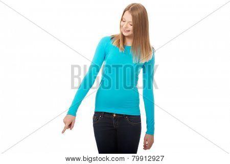 Happy teenage woman pointing down