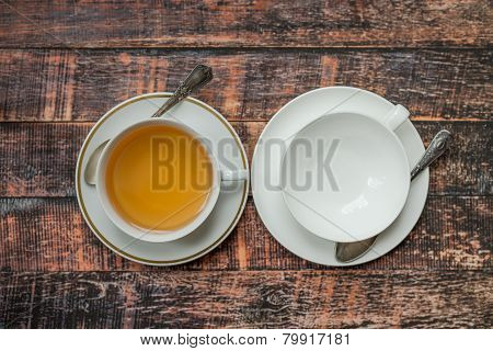 Full And Empty Cups Of Tea On Old Wooden Table