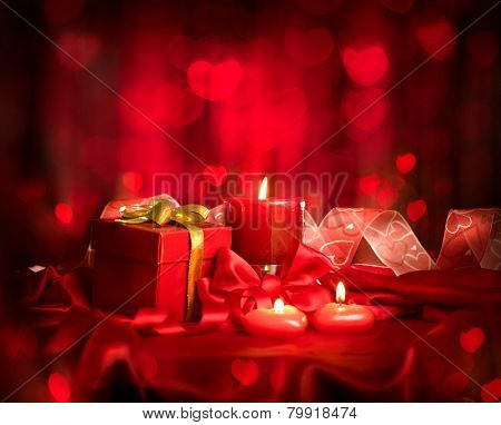 Valentine's Day. Valentine Red Heart shaped candles and Gift on Red Silk over glowing background. Beautiful Valentine card art design