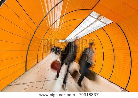 People rushing through a subway corridor (motion blur technique is used to convey movement)
