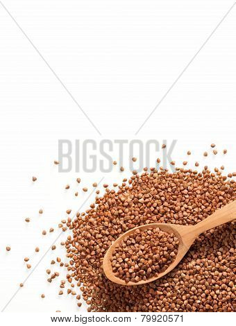Heap of buckwheat groats and wooden spoon