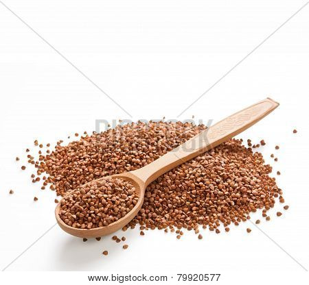 Wooden spoon on a heap of buckwheat groats