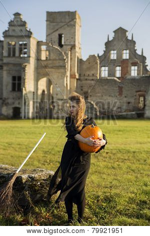 Witch With Pale Skin Embraces Pumpkin