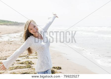 Young blonde carefree woman with arms outstretched on Atlantic beach in Prince Edward Island, Canada