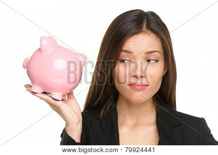 Piggy bank savings with unhappy funny woman looking displeased at pink piggy bank isolated on white background. Business woman or banker wearing suit jacket. Mixed race Asian Caucasian female model.