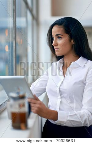 Young business woman investor using tablet computer for work in office with coffee
