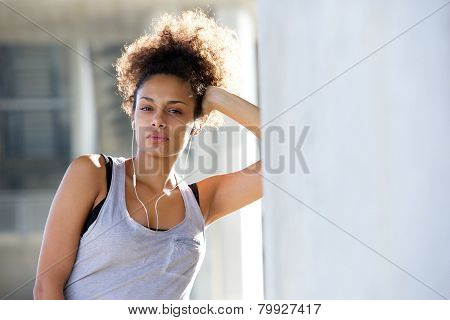 Relaxed Young Woman Leaning Against Wall