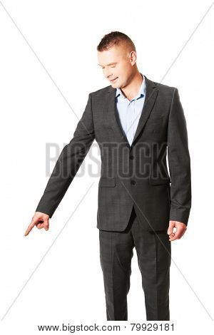 Young smiling businessman pointing down.