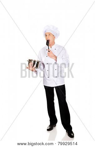 Experienced chef in white uniform tasting his soup