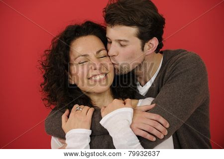 Valentines day: Happy man kissing woman on red background