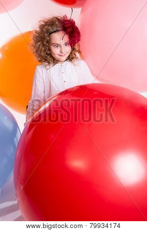 Young Teen Girl In A Hat And White Dress On A Background Of Big Colored Rubber Air Balls