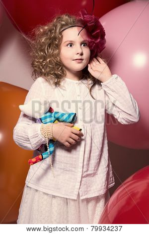 Surprised Girl In A Red Hat In A White Dress With A Soft Toy In His Hand Looking To The Side