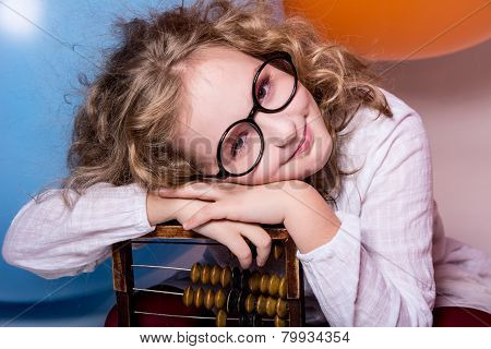 Funny, Clever Curly Teen Girl In Glasses With Wooden Abacus On The Background Of Large Rubber Balls