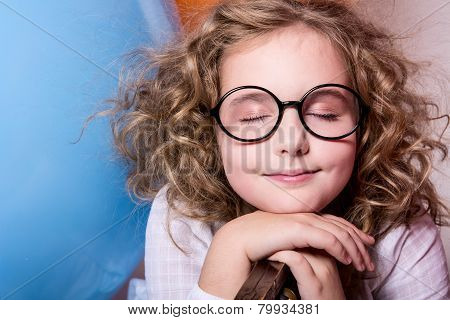 Portrait Of Teen Girl Dreaming In Glasses With Eyes Closed Against The Background Of Large Rubber Ba