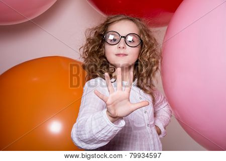 Portrait Of A Teenage Schoolgirl Showing Five Fingers On A Background Of Large Rubber Balls.