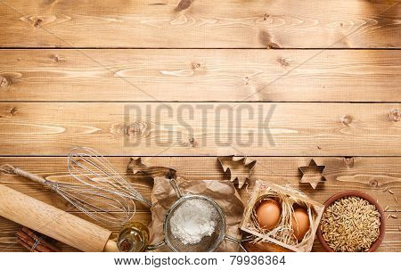 Ingredients for baking on empty light wooden background with pla