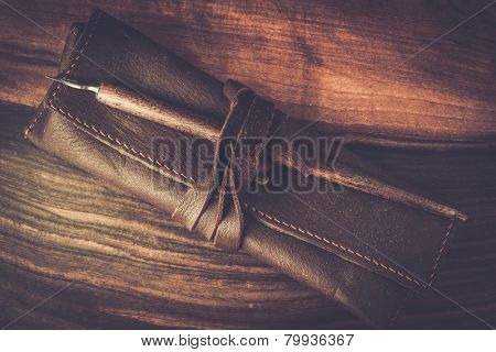 Quill pen with leather case on wooden background