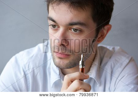 Young Man Smoking Vapor Cigarette