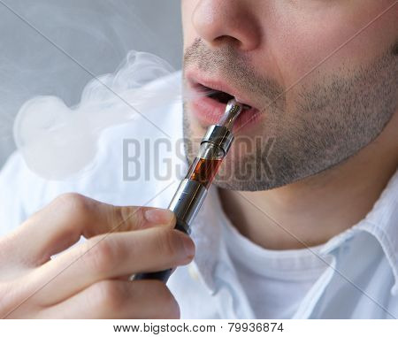 Young Man Exhaling Smoke From Electric Cigarette
