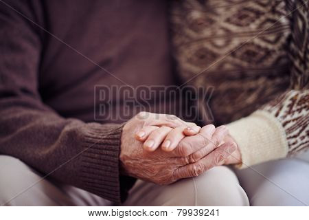 Hands of devoted seniors