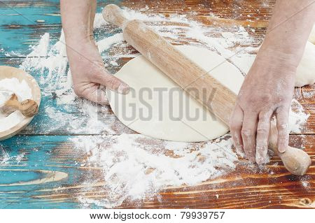 Woman rolling dough using rolling pin